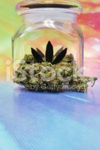 Medical marijuana in a jar with rainbow background