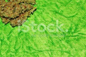 Cannabis on a green background closeup horizontal