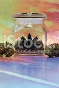 Medical marijuana in a jar with rainbow background vertical
