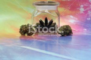 Medical marijuana in a jar with rainbow background horizontal