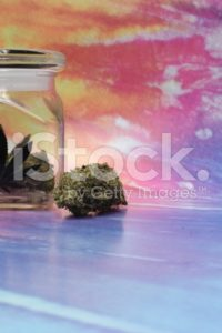 Medical marijuana in a jar with rainbow background image left